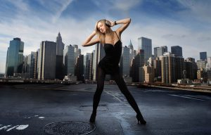 Blonde girl with bluetooth headphones striking a pose with cityscape in the background